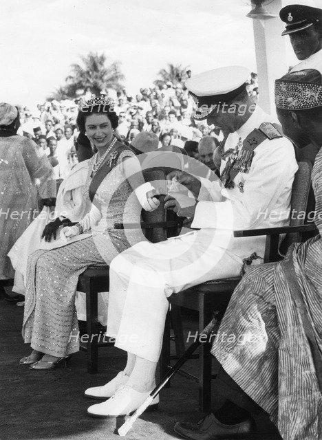Queen Elizabeth shows Prince Philip a gift, Port Loko, Sierra Leone, 1961. Artist: Unknown