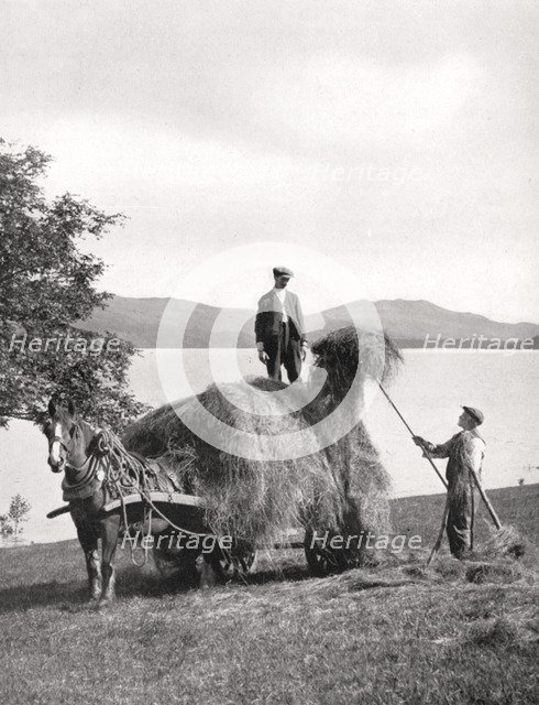 Loading hay onto a wagon on the shores of Loch Lomond, Scotland, 1924-1926.Artist: Donald McLeish