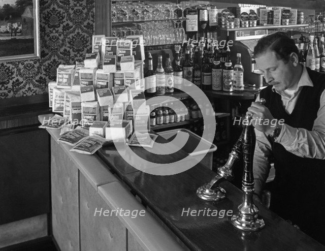 A pub landlord with a display of the Batchelors 5 day catering pack on his bar, 1968. Artist: Michael Walters