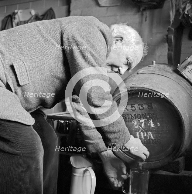 An elderly Gloucestershire man pouring a pint of beer, c1946-c1949. Artist: John Gay