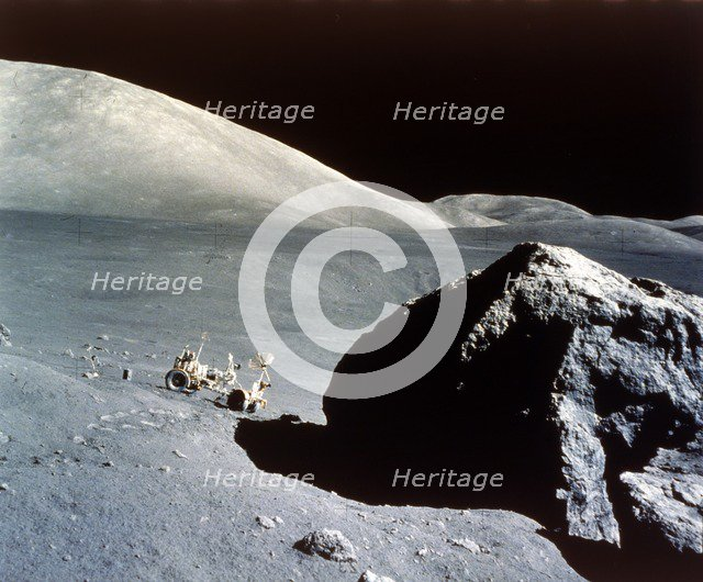 The Rover is dwarfed by a giant rock on the lunar surface, Apollo 17 mission, December 1972. Creator: NASA.