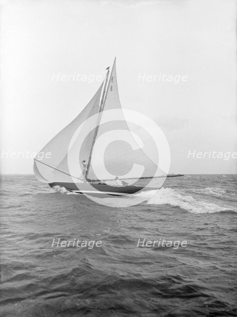 The 7 Metre yacht 'Pinaster' (K8) sailing with spinnaker, 1913. Creator: Kirk & Sons of Cowes.