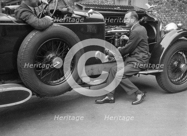 Geoffrey Baker inspecting the engine of a Minerva car. Artist: Bill Brunell.