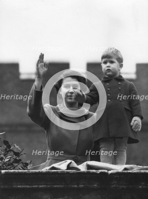 Princess Elizabeth and a two year old Prince Charles wave from Buckingham Palace, 1950. Artist: Unknown