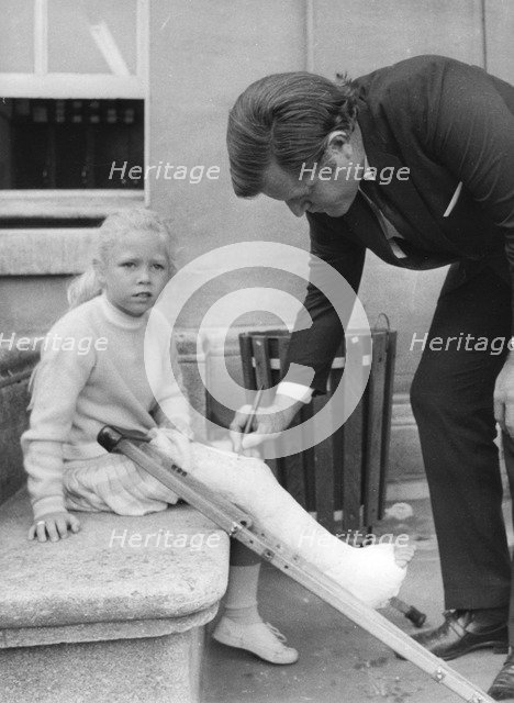 Senator Edward Kennedy signs a girl's leg cast at Radcliffe Infirmary, Oxford, 1971. Artist: Unknown