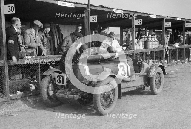 Clive Gallop and Leon Cushman's Aston Martin in the pits, JCC Double Twelve race, Brooklands, 1931. Artist: Bill Brunell.